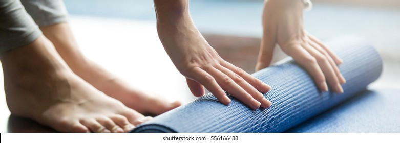 Close-up of woman folding blue yoga or fitness mat after working out at home in living room. Healthy life, keep fit concepts. Horizontal shot. Horizontal photo banner for website header design