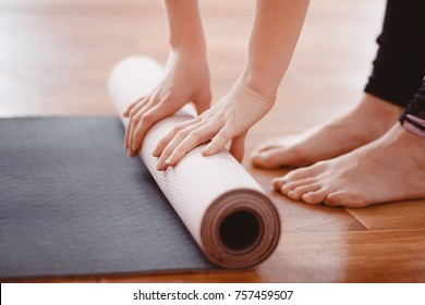Close-up woman folding roll fitness or yoga mat after working out home in living room. Concept healthy life.