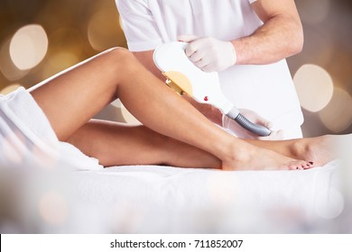 Close-up Of A Woman Getting Laser Treatment On Leg By Therapist