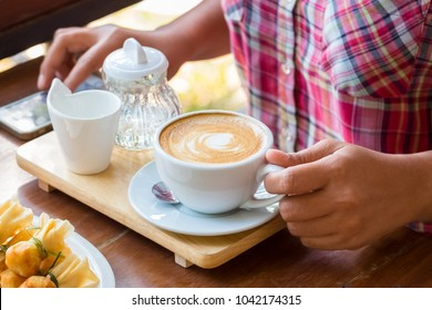 Closeup woman going to drink coffee on dining table while use the smart phone