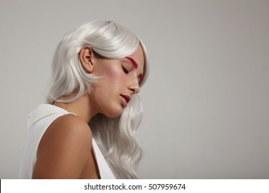 closeup of woman with grey white hair and pink makeup