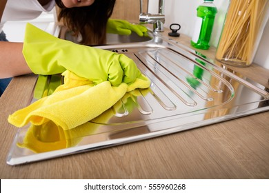 Close-up Of Woman Hand Cleaning Stainless Steel Sink With Cloth In The Kitchen