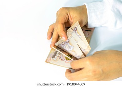 Close-up, woman hand counting Thai banknote money on white background, to spend on purchases and pay off debts during the covid-19 crisis.
