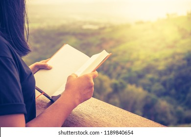 Closeup woman hand hold the book to read at the edge of balcony with sunlight over the hill