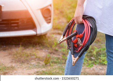 Closeup of woman hand holding battery cable copper wire for repairing broken car by connect battery with red and black line to electric terminal by herself. Car maintenance and transportation concept