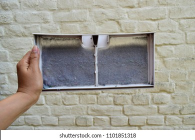 Closeup of woman hand holding debris dirty on air filter of dryer machine against old wall background and waiting to clean it.