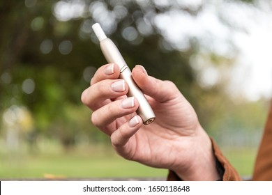 Close-up of woman hand holding a heat not burn tobacco product. Smoke free product that uses sophisticated electronics to heat tobacco instead of burning it.