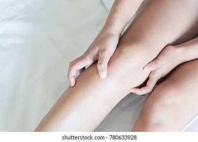 Closeup woman hand holding knee with pain on bed, health care and medical concept