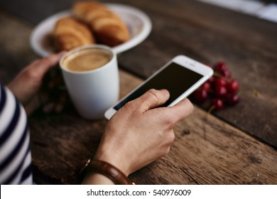 Close-up of woman hand holding smart phone, reading morning news during breakfast. Concept of device and connection.