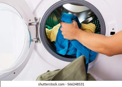 Close-up Of Woman Hand Loading Dirty Clothes In Washing Machine