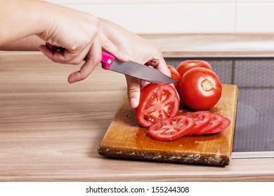 Closeup of woman hand preparing tomato in the kitchen.