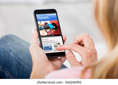 Close-up Of Woman Hand Reading News On Mobile Phone At Home