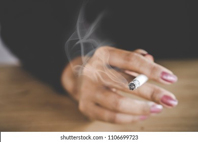 closeup woman hand smoking cigarette ,unhealthy lifestyle concept