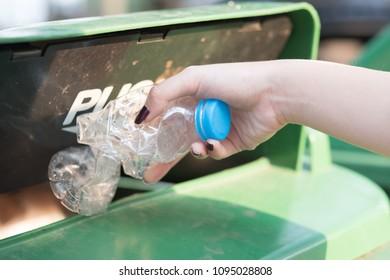 Closeup woman hand throwing empty plastic bottle into recycling bin