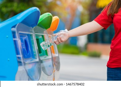 Closeup woman hand throwing empty plastic water bottle into to recycling bin, environmental protection concept.