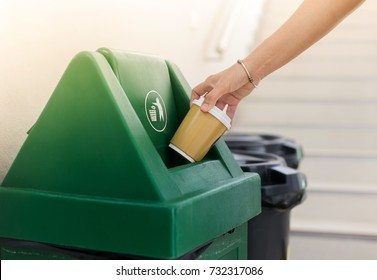 Closeup woman hand throwing empty paper coffee cup in recycling bin.