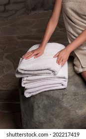 Closeup of a woman hand touching stacked white spa towels on stone wall background