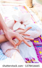 closeup of woman hand in yoga mudra gesture sit in lotus posture outdoor sunny spring summer day