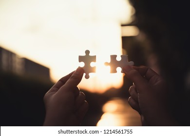Closeup of woman hands connecting jigsaw puzzle on sunset scene, Business solutions, success mission concept.