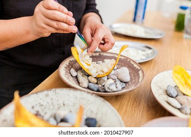 Closeup of woman hands cooking banana chifles with fake squid noodles and beluga caviar