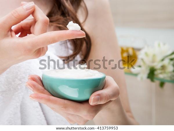 Primo piano delle mani delle donne che tengono una ciotola con maschera nutriente per l'applicazione su capelli o pelle; concetto di bellezza e spa