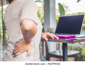 Closeup woman with hands holding her waist back in pain. Office syndrome and Health-care Concept.