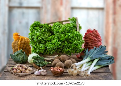 Closeup of woman hands holding a large wooden crate full of raw freshly harvested salad vegetables with salad field on background