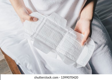 Closeup of woman hands holding sanitary napkins or menstruation pad before wearing it. Women using it during menstruation to avoid damage to clothing
