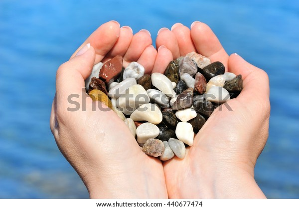 Closeup of woman hands holding sea pebbles form heart shape