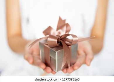 Closeup of woman hands holding a small gift box for special event. Christmas, birthday or new year concept.