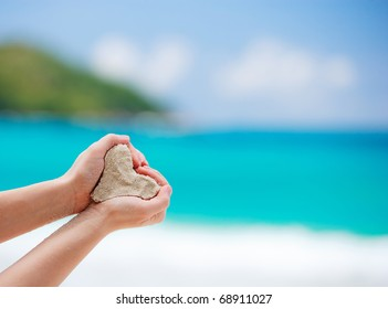 Closeup of woman hands holding white tropical beach form heart shape