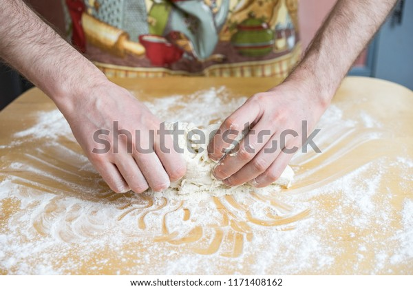 Closeup of woman hands kneading dough on the kitchen table.