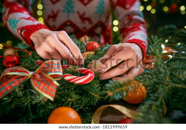 close-up of a woman hands making handmade christmas wreath on table for holiday. Christmas decoration and composition.