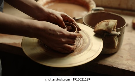 Closeup woman hands modeling clay product in pottery. Unrecognized lady sculpting wet clay in workshop. Unknown girl working with potters wheel in studio.