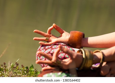 closeup of woman hands in mudra gesture practice yoga meditation outdoor by the lake summer day