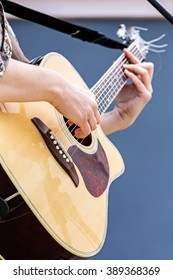 closeup of woman hands playing acoustic guitar outdoors