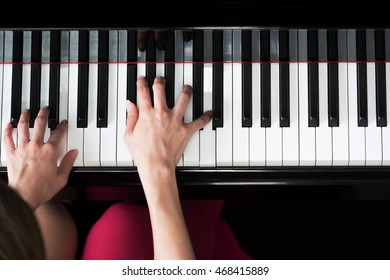 Close-up of woman hands playing and practicing piano - top view