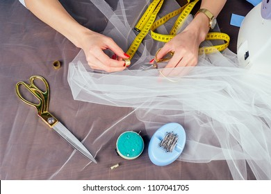 closeup woman hands tailor wedding dressmaker (seamstress) sew on the sewing machine on a blue background in the studio. The concept of creating a new collection of wedding dress