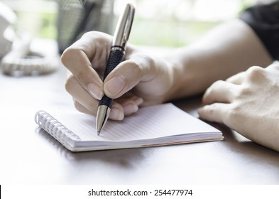 closeup of woman hands taking note