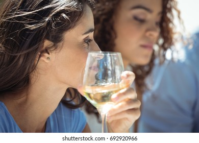 Close-up of woman having glass of wine in restaurant