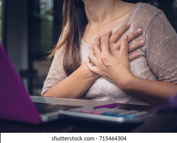 Closeup woman having heart attack. Woman touching breast and having chest pain after long hours work on computer. Office syndrome concept.