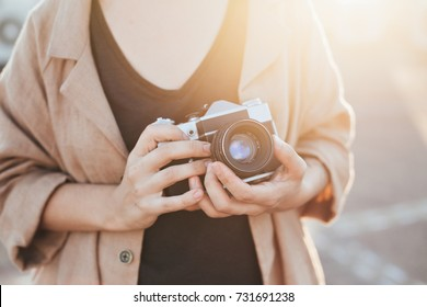 Closeup of woman in hipster outfit, holding vintage analog film camera, zooming and focusing in warm soft evening sunlight