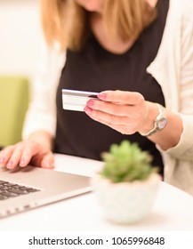 closeup of woman holding credit card at home in front of laptop computer - soft focus for effect