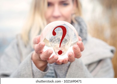 closeup of woman holding a glass ball with a question mark