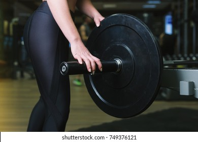 Close-up of a woman holding her hands with a barbell for pulling, squatting, fitness in the gym. Concept sports, toned picture, copyspace for text