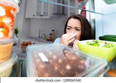 Close-up Of A Woman Holding Her Nose Near Foul Food In An Open Refrigerator