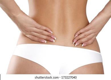 Closeup of a woman holding her painful back on white