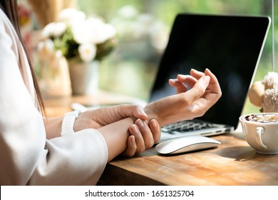 Closeup woman holding her wrist pain from using computer. Office syndrome hand pain by occupational disease.