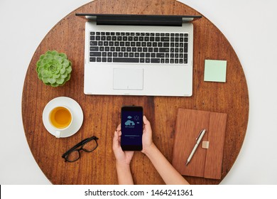 Close-up of woman holding mobile phone and downloading photos in My cloud while sitting at wooden table in front of laptop