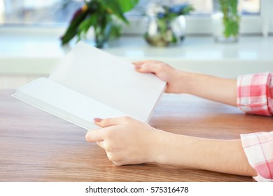Closeup of woman holding opened book